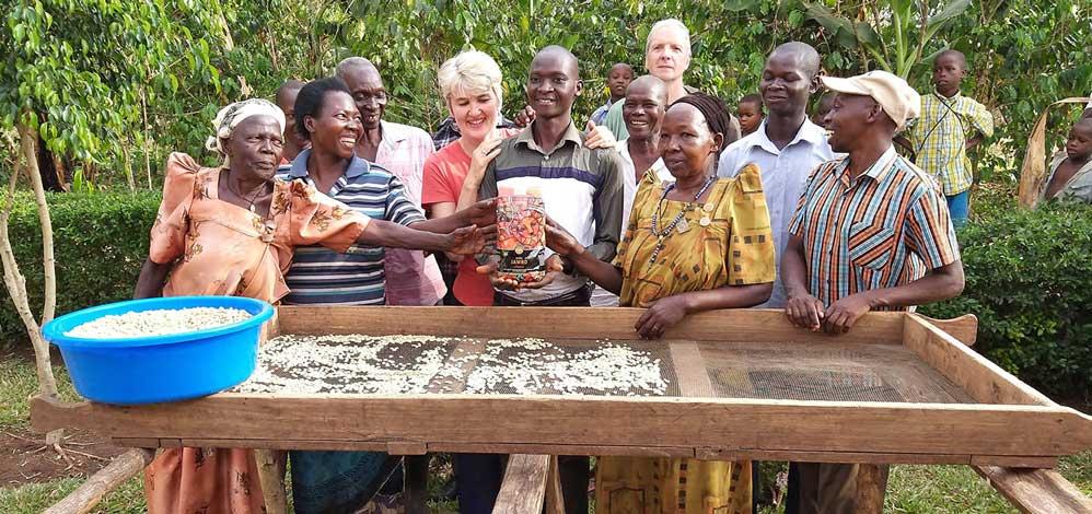 """Ema, der junge Kaffeebauer in der Mitte hält eine Packung bio-fairen """"Kaffee Jambo"""" in Händen; Seine Bohnen, die vor der Gruppe in der Sonne trocknen, sind in diesem Kaffee drinnen. Links von ihm Andrea Schlehuber, Geschäftsführerin der EZA Fairer Handel."""